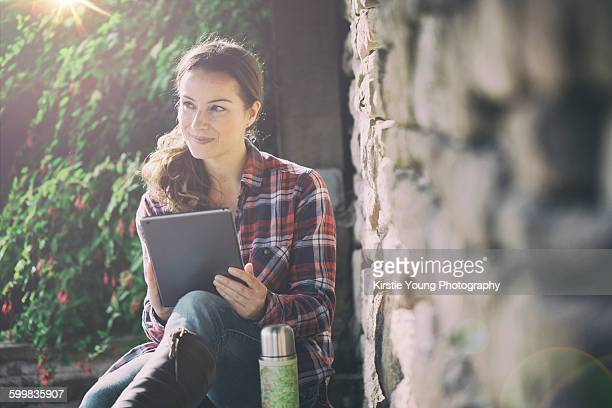 Mid adult woman using digital tablet in gardens at Thornbury Castle, South Gloucestershire, UK