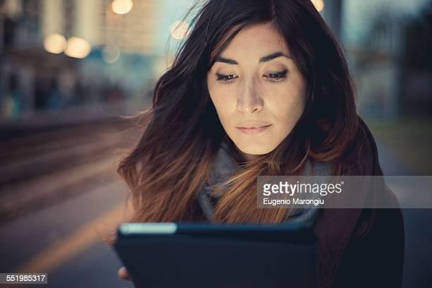 Mid adult woman using digital tablet touchscreen on railway platform at dusk