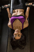 Mid adult woman using dumbbells for abdominal exercise