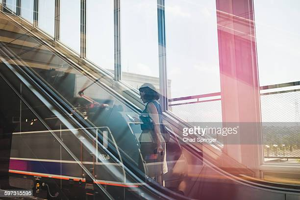 Mid adult woman using escalator, holding wheeled suitcase and smartphone