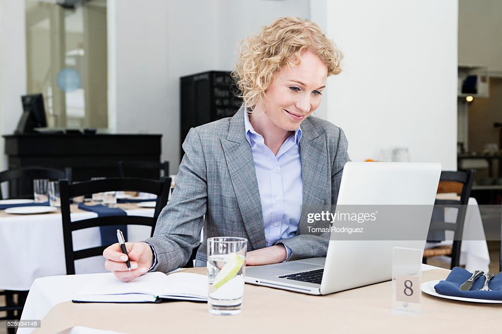 Mid adult woman using laptop at restaurant table : Stock Photo
