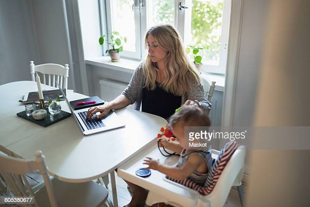 Mid adult woman using laptop while taking care of baby boy at home