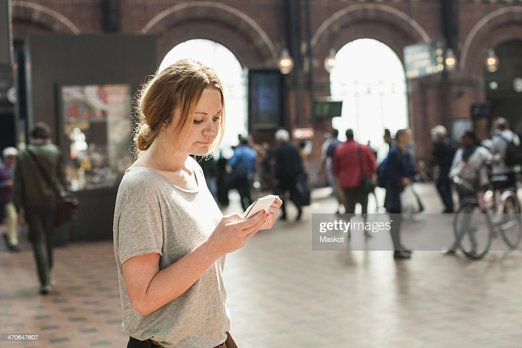 Mid adult woman using mobile phone on railway station