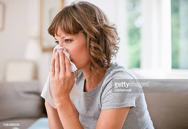 Mid adult woman using napkin for sneezing her nose
