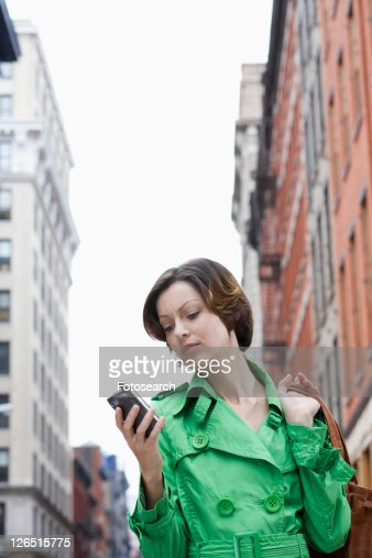 Mid adult woman using PDA on street, low angle view