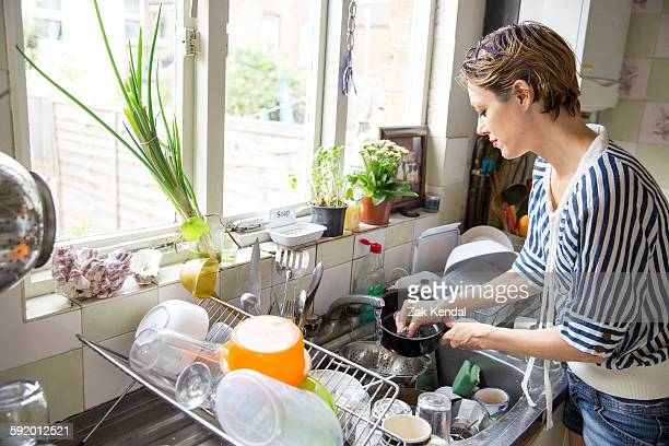 Mid adult woman washing up at kitchen sink