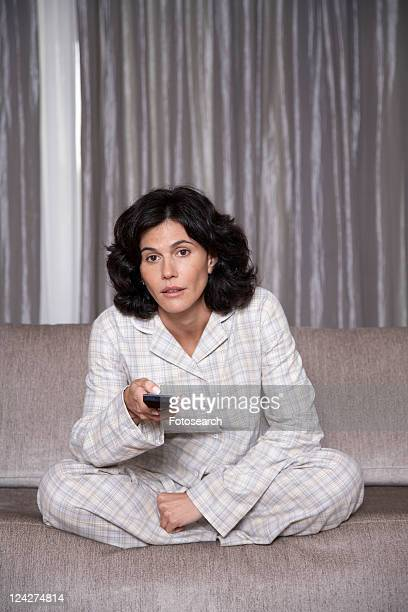 Mid adult woman watching TV on sofa