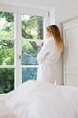 Mid adult woman wearing bathrobe looking out of window
