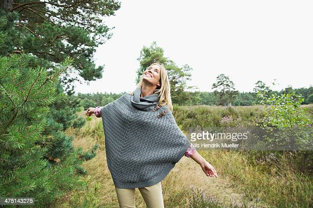 Mid adult woman wearing grey poncho looking up