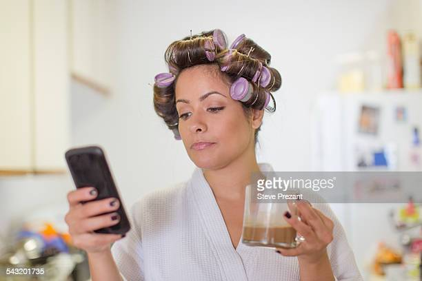Mid adult woman wearing hair rollers and reading text message on smartphone