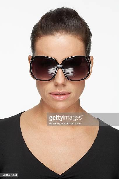 Mid adult woman wearing oversize sunglasses, portrait