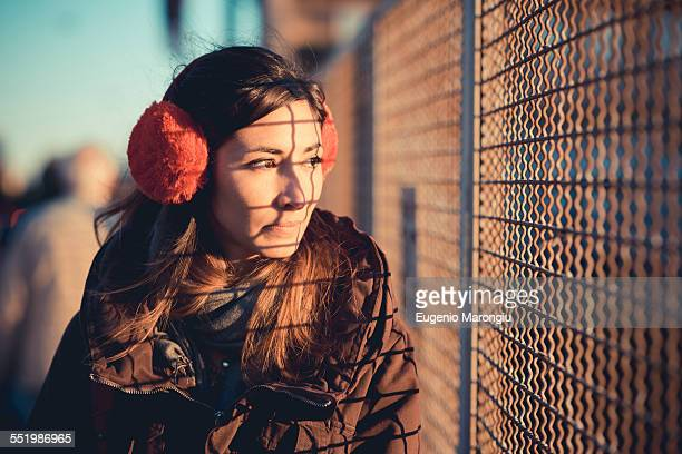 Mid adult woman wearing red ear muffs gazing through sunlit wire fence