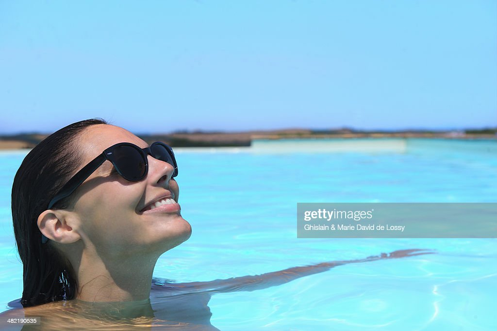Mid adult woman wearing sunglasses relaxing in pool : Stock Photo