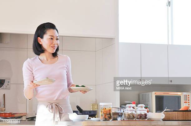 Mid Adult Woman with Apron Serving Dishes