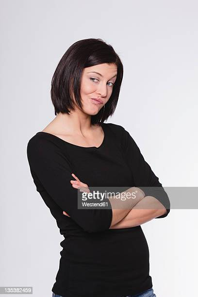 Mid adult woman with arms crossed and grimacing against white background