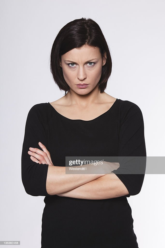 Mid adult woman with arms crossed and staring against white background