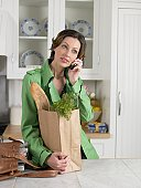 Mid adult woman with bag of groceries talking on phone