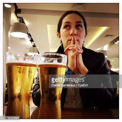 Mid Adult Woman With Beer Glasses At Pub