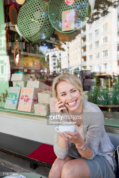 Mid adult woman with coffee cup making smartphone call at city sidewalk cafe