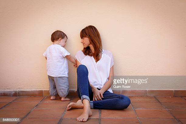 Mid adult woman with curious baby daughter on kitchen floor