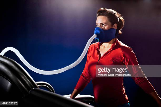 Mid adult woman with face mask on gym treadmill in altitude centre