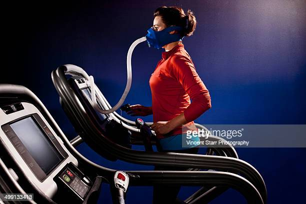 Mid adult woman with face mask running on gym treadmill in altitude centre