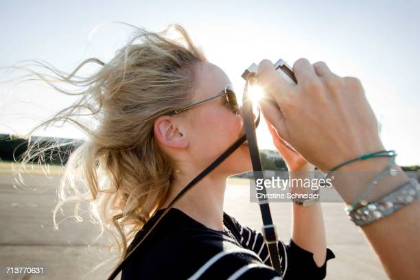 Mid adult woman with flyaway hair taking photographs on vintage camera
