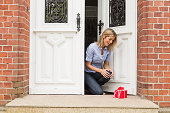 Mid adult woman with gift on front doorstep