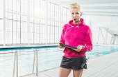 Mid adult woman with headset at swimming pool