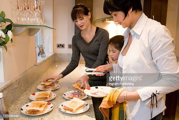 Mid adult woman with her two daughters preparing sandwiches