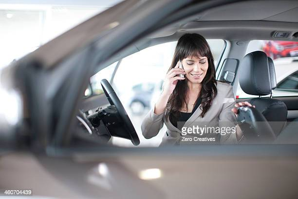 Mid adult woman with mobile phone in car showroom
