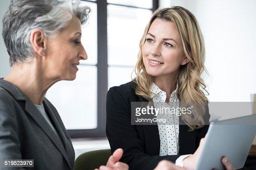 Mid femme adulte avec ordinateur portable souriant de mature collègue