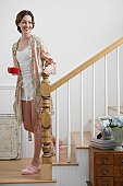 Mid adult woman with tea cup walking down stairs in morning