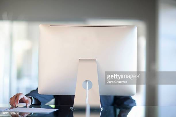 Mid adult woman working behind computer at desk