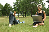 Mid adult woman working on a laptop with a man lying in the grass beside her