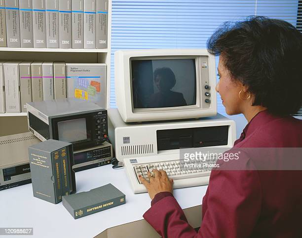 Mid adult woman working on old computer and watching video