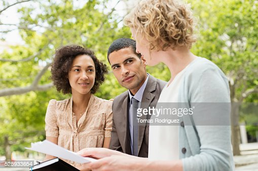 Mid adult women and men discussing in park : Foto stock
