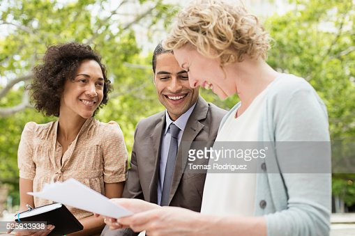 Mid adult women and men discussing in park : Stock Photo
