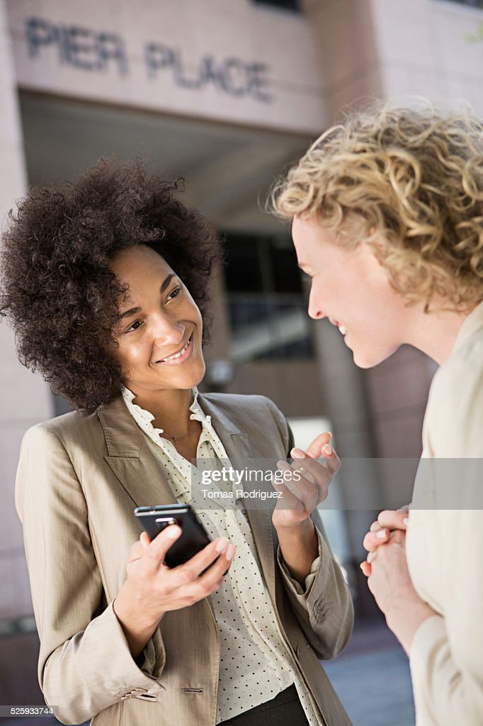 Mid adult women talking on street : Stock-Foto
