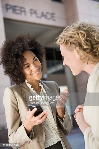 Mid adult women talking on street : Stock Photo