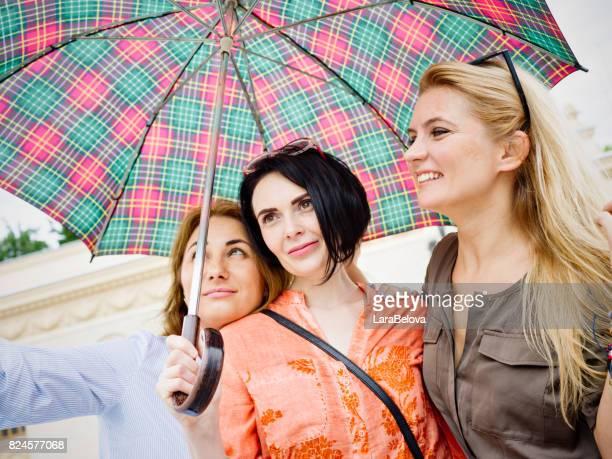 Mid adult women under umbrella in the city