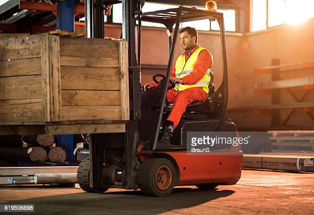 Mid adult worker driving forklift with palette in distribution warehouse.