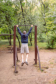 Mature Athlete Doing Pull-ups on Horizontal Bar in Public Park on Cold Rainy Day and Listening to Music