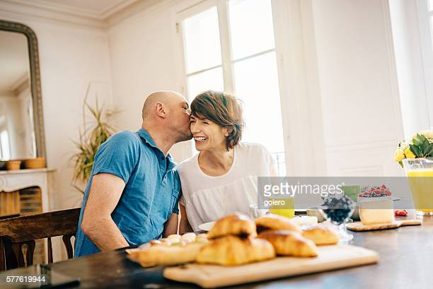 mid aged man kissing wife at holiday breakfast table