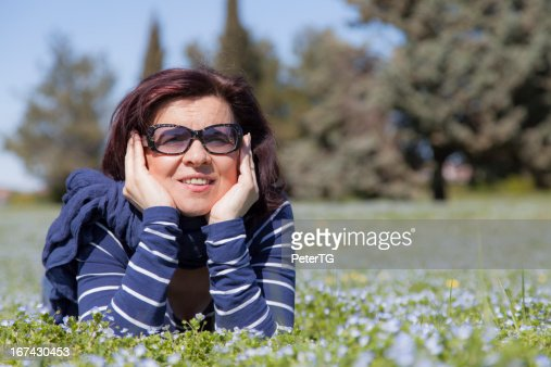 Mid aged woman relaxing on grass : Stock Photo