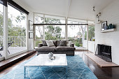 Mid century modern living room with huge windows to view the Australian treetops