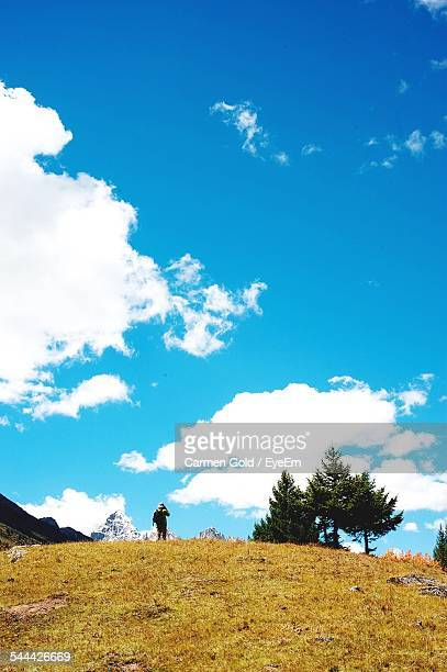 Mid Distance Of Hiker Standing On Hill Against Cloudy Sky