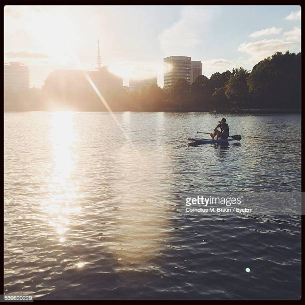 Mid Distance Of Man Sitting On Paddleboard On Lake