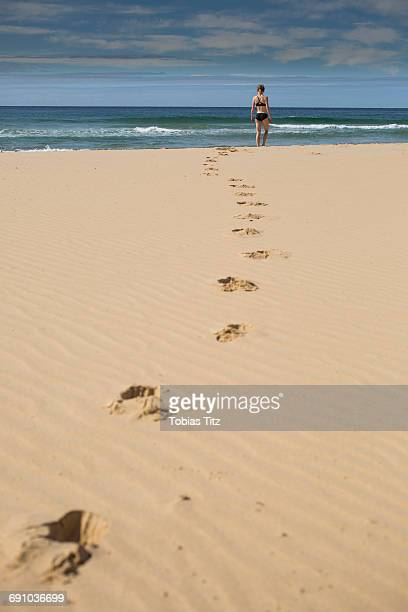 Mid distance of woman at beach against sky