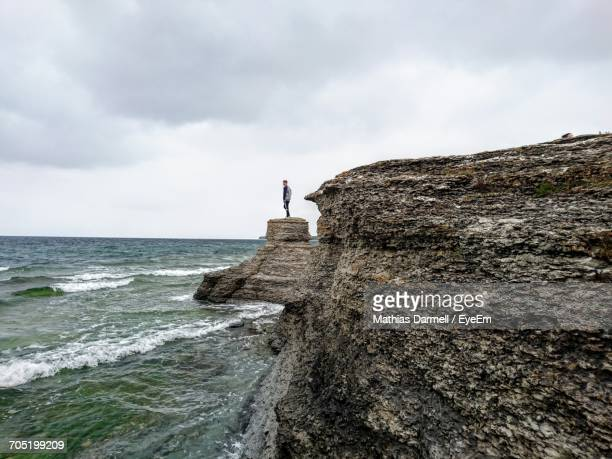 Mid Distance View Of Man Standing On Cliff By Sea Against Cloudy Sky At Byrums Raukar
